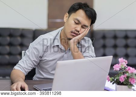 Asian Business People Are Feeling Stressed About The Job With Laptop And Paper On The Wooden Table I
