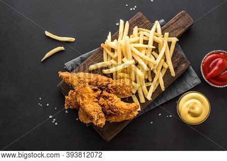 Fish And Chips. Deep Fried Fish Filet And With French Fries Served On Black Table With Sauces. Tradi