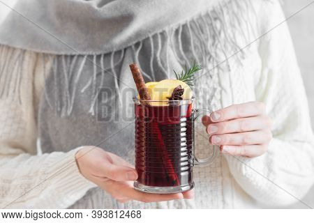 Woman Holding Mug Of Hot Mulled Wine. Female Hands With Cup Of Seasonal Winter Hot Drink. Homemade F