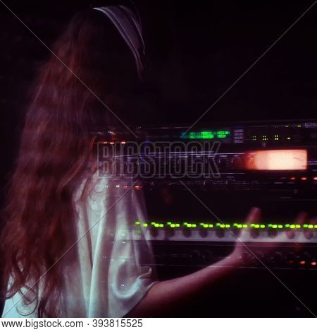 A Girl In A White Dress With Long Hair Sings Behind A Microphone. Professional Singer Performs Vocal