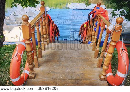 Entrance To The Boat Station In The Park. Life Jackets On The Railing. Dock With Paddle Boats In Sum