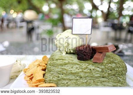 In Selective Focus A Green Tea Big-su Dessert On White Outdoor Table With Blurred Tree Roof View And