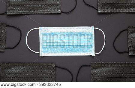 Blue Medical Mask, Protective Face Mask On Black Background With Black Masks. Disposable Surgical Fa