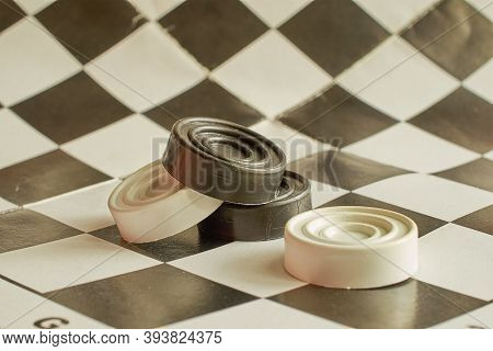 Board Game Checkers. A Checkered Board And Four Checkers