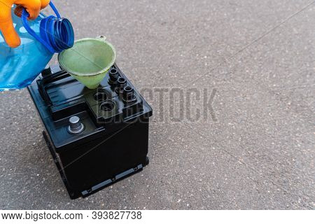 Mechanic Adds Electrolyte From A Canister To The Battery, Diagnostics And Repair Of A Car Battery