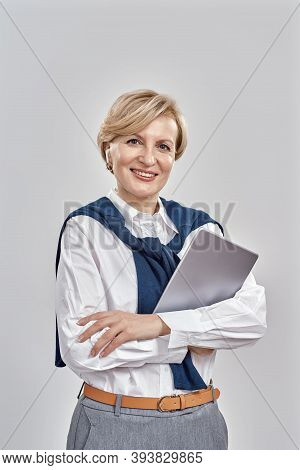 Portrait Of Elegant Middle Aged Caucasian Woman Wearing Business Attire Smiling At Camera, Holding T