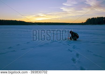 Winter Landscape. A Man Is Fishing On A Winter Evening.