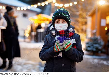 Kid Boy Drinking Hot Children Punch On German Christmas Market. Happy Child With Medical Mask . Peop