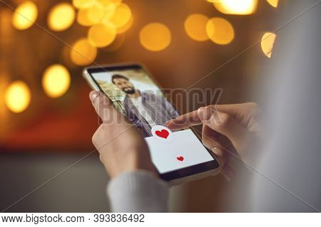 Closeup Of Woman Looking At Young Mans Profile Photo On Dating App And Pressing Like Button