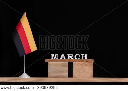 Wooden Calendar Of March With German Flag On Black Background. Dates In Germany In March