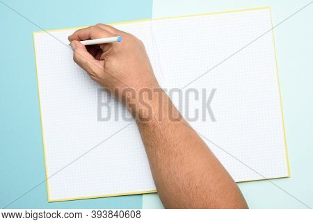 Male Hand Holding Open Notepad With Empty White Sheets On A Blue Background, Top View