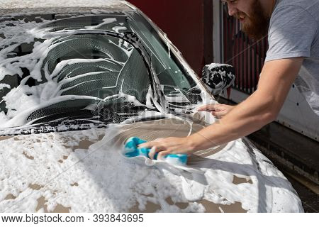 Male Motorist Washing Car With A Washcloth And Shampoo, Auto Covered With Foam, Self-service Car Was