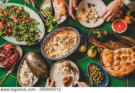 Family Having Turkish Dinner. Flat-lay Of People Hands Eating Lamb In Yogurt Sauce, Arugula And Stra