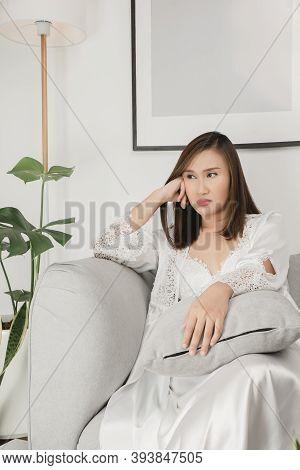 Asian Women Wearing White Satin Sleepwear Sitting On A Gray Sofa Looking Sideways. Absent-minded Fem