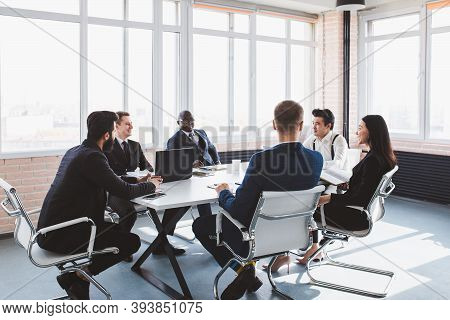 Group Of Young Business People Working And Communicating While Sitting At The Office Desk Together W