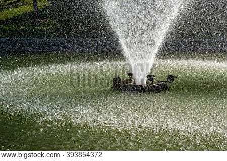 View Of A Water Fountain Spraying Water In A Pond In A Public Park.