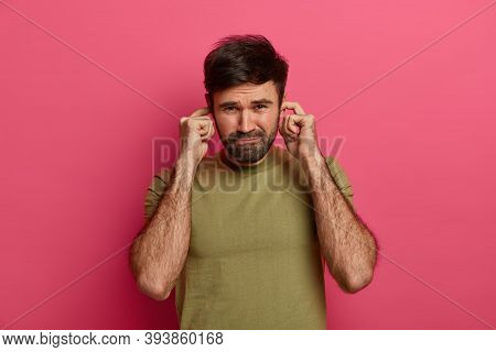 Displeased Bearded Man Unwilling Listen To Friends Conversation, Plugs Ear Holes With Fingers, Canno
