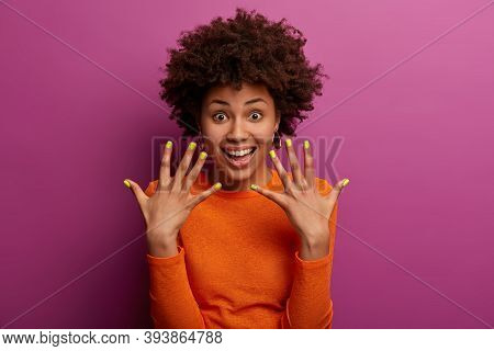 Curly Ethnic Woman Shows Manicured Yellow Nails, Has Glad Expression, Smiles Happily, Glad After Vis
