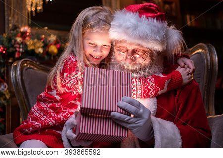 Santa Claus And Girl Opening Christmas Gift Near Christmas Tree. Child Hugging Santa. Magic Fulfillm