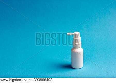 White Jar Of Medical Throat Spray On A Blue Background.
