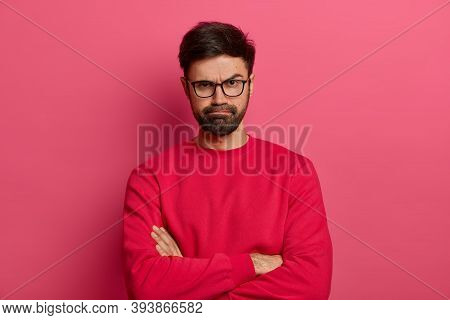Portrait Of Attractive Bearded Young Man Keeps Hands Crossed, Makes Negative Opinion About Something