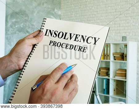 The Man Reads The Insolvency Procedure In The Book.