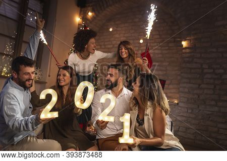 Group Of Young Friends Having Fun At New Year's Party, Holding Illuminative Numbers 2021 Representin