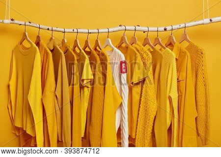 Shopping And Special Offer Concept. Many Yellow Clothes Items And White Knitted Sweater With Red Tag