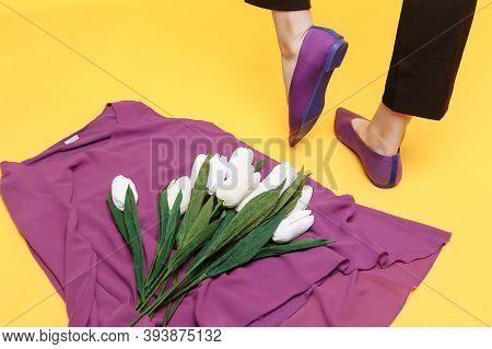 Beautiful Female Legs Are Dressed In Stylish Violet Flat Shoes. Violet Sandals On A Yellow Backgroun