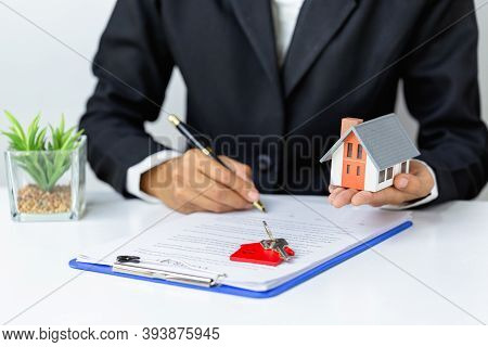 A House On The Hand Of A Businessman And The Hand Is Signing A Home Purchase Contract. Holding A Pen