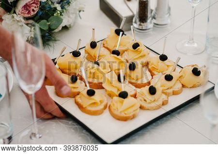 The Waiter Puts A Plate On The Table With Gourmet Appetizers, Variety Of Mini Sandwich, Crostini Wit