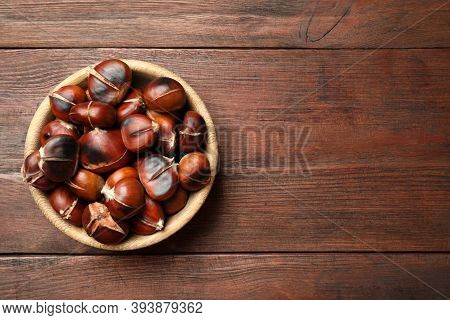Delicious Roasted Edible Chestnuts On Brown Wooden Table, Top View. Space For Text