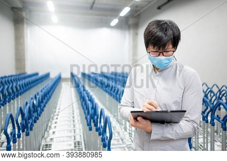 Asian Man Worker Wearing Face Mask Doing Stocktaking In Warehouse By Using Clipboard. Physical Inven