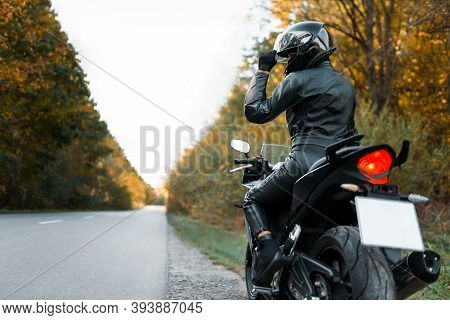 Motorcyclist In Leather Outfit On The Roadside