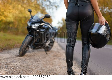 Female Motorcyclist In Leather Clothes Stands On The Side Of The Road Holding Helmet In Hand