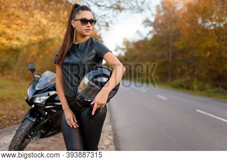 Brutal Female Motorcyclist In Glasses Stands Near Motorcycle On Roadside And Holding Helmet