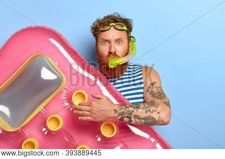 Photo Of Redhead Ginger Man Wears Swim Goggles, Snorkeling Mask, Going To Dive And Swim In Sea, Hold