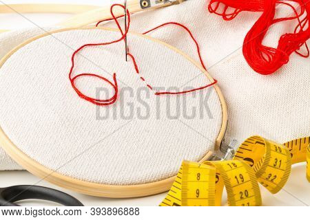 Round Stitching Or Embroidery Frame With Red Stitching And Sewing Tools, Selective Focus