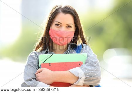 Front View Portrait Of A Happy Student With Mask Posing In The Street
