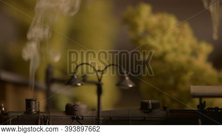 Steam Lokomotive And Blurred Background. Close-up Plastic Miniature Pole Lamp With Vapor And Trees.