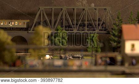 Model Of Retro Lokomotive On The Bridge. Miniature Train With Smoke.
