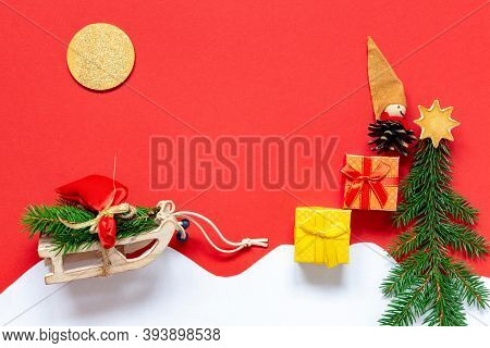 Christmas Scene With Doll Elf And Sledge And Gifts And Spruce Tree On Red Background