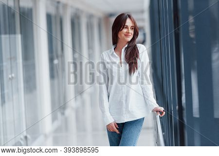 Brunette In White Shirt Indoors In Modern Airport Or Hallway At Daytime.