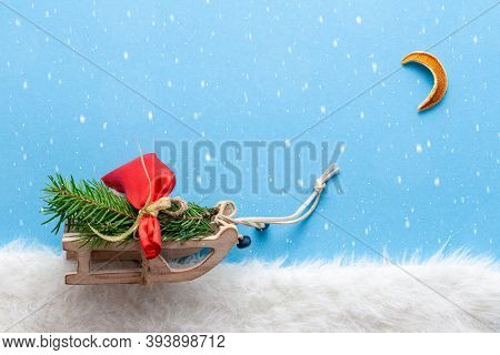 Fairy Tale In Forest With Toy Sledge And Bag Of Gifts With Christmas Tree And Moon During On Xmas Ev
