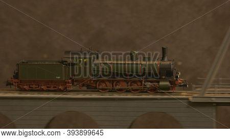 Side View Lokomotive Train On The Bridge. Replica Of Retro Train Model On A Railway Station.
