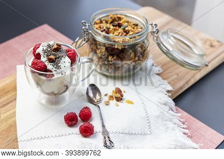 Granola In A Jar And In A Cup With Yogurt And Raspberry On The Table. Granola Is A Breakfast Food An