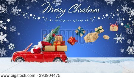 Santa Claus In Red Toy Car Delivering Christmas Presents Or New Year Gifts On Blue Winter Background