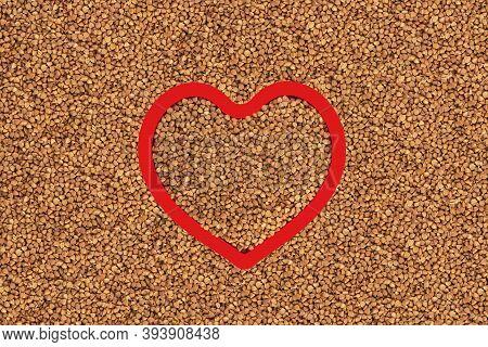 Brown Buckwheat Groats In Heart Shape Red Frame.