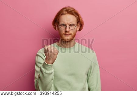Outraged Bearded Man With Bob Hairstyle, Clenches Fist, Frowns From Insult And Displeasure, Expresse