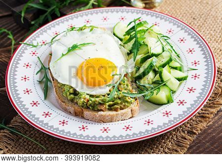 Healthy Breakfast. Christmas Brunch. Avocado Sandwich With Fried Egg And Cucumber With Arugula On Wo